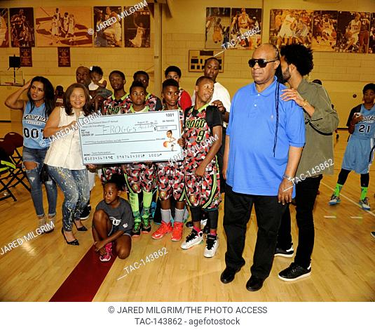 Stevland Morris aka Stevie Wonder (r) and wife Kai Millard Morris (l) present Frogg Allstars with a $500 check at the 3rd Annual Kailand Obasi Hoop-Life at the...