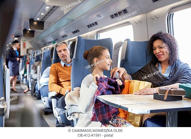 Mother and daughter looking at new clothes on passenger train