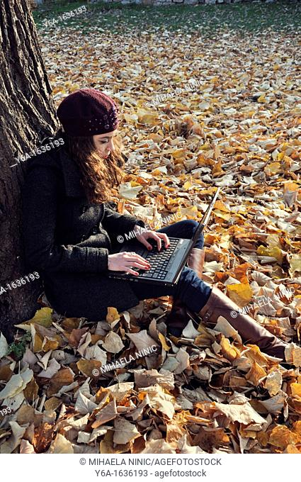 Young woman outdoors sitting on autumn leaves using laptop