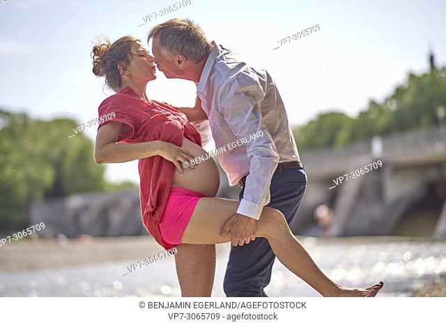 Couple dancing, pregnancy, age difference, love, freedom. At river Isar, Munich, Germany