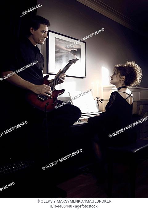 Young couple playing music in romantic dimly lit room, woman is playing piano and a man playing guitar