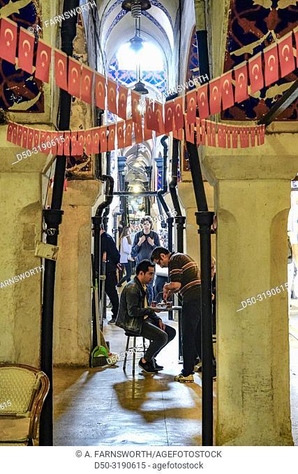 Istanbul, Turkey Two men in the Grand Bazaar sit between columns