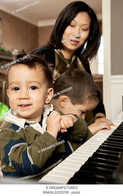 Asian mother teaching sons to play piano