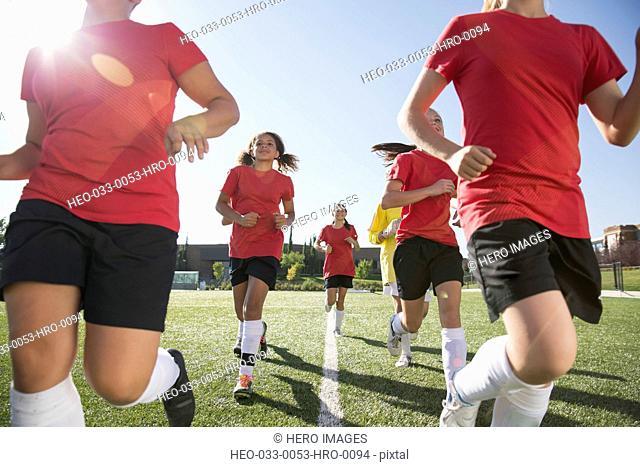 Girls soccer team running on field