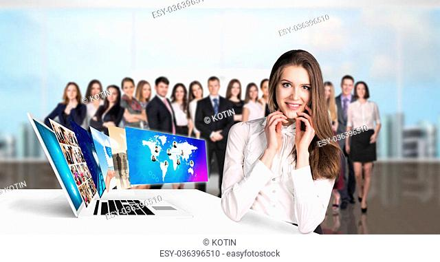 Young business woman stands near table with laptop. Elements of this image furnished by NASA