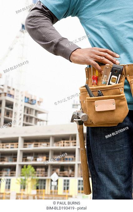 Black construction worker wearing tool belt