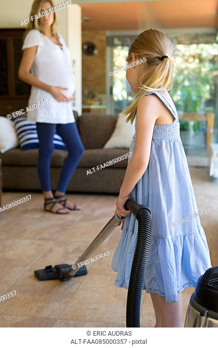 Little girl vacuuming, pregnant mother in background