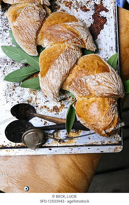 Braided bread on a baking tray with fresh herbs on a chair