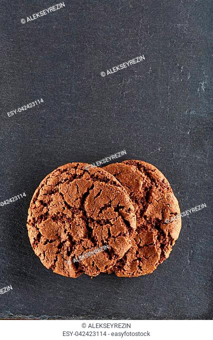 Freshly baked chocolate chips cookies isolated on black background, macro, close-up, vertical