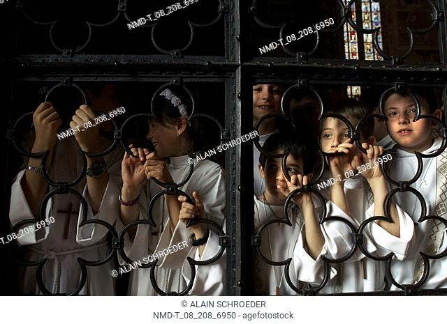 Group of children looking through the window of a church, Orvieto, Umbria, Italy
