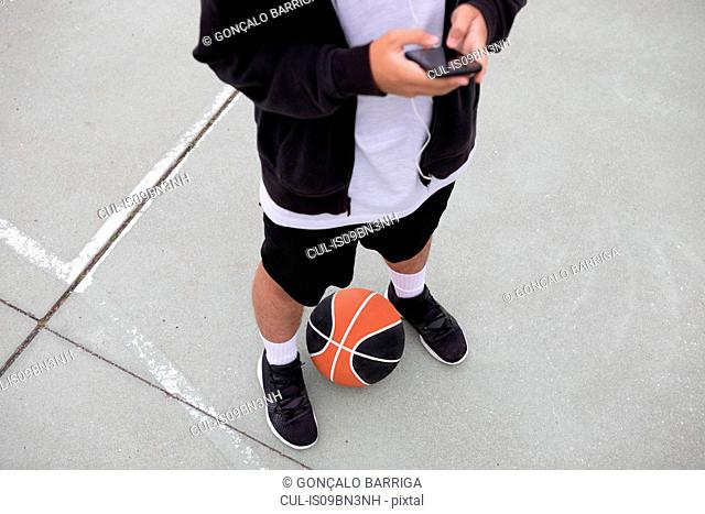 Male teenage basketball player standing on basketball court looking at smartphone, waist down