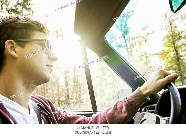 Young man leaning driving convertible on country road