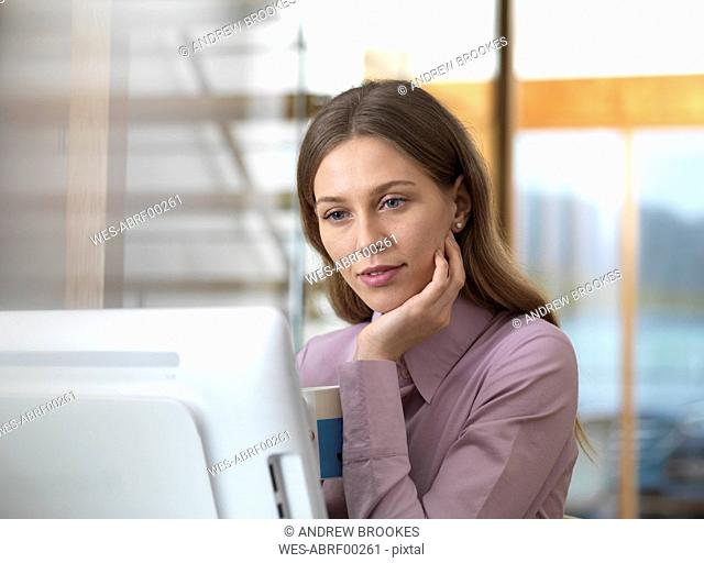 Businesswoman in office holding cup looking at PC