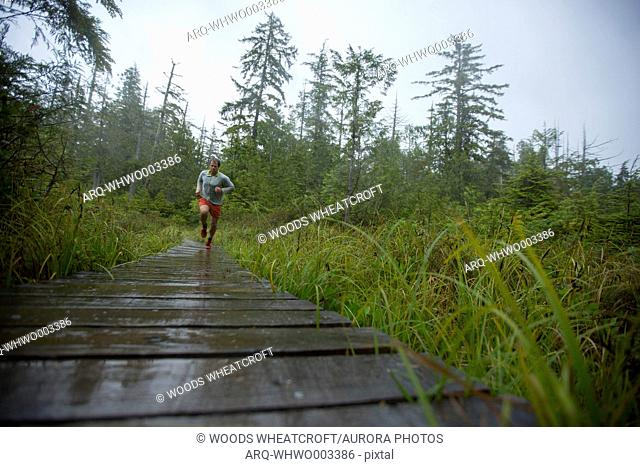 Low angle image of an adult man running on a boardwalk in the rain in the Lake Ozette-Cape Alava area of Olympic National Park, Washington