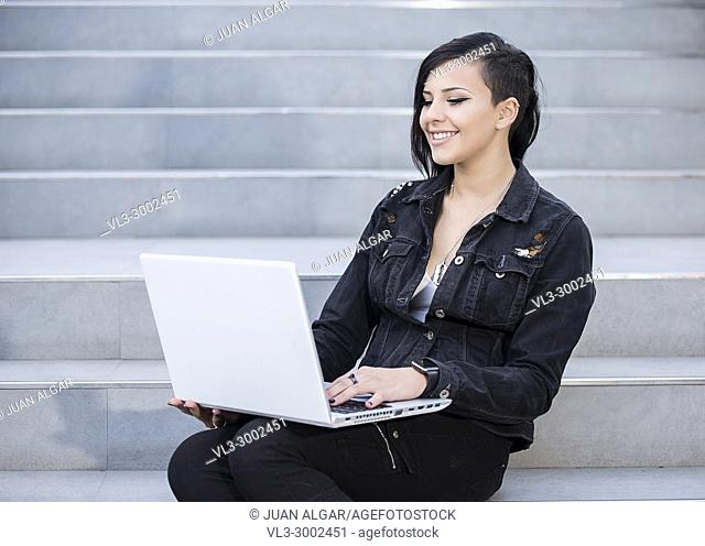 Smiling casual dressed woman sitting on steps and using laptop
