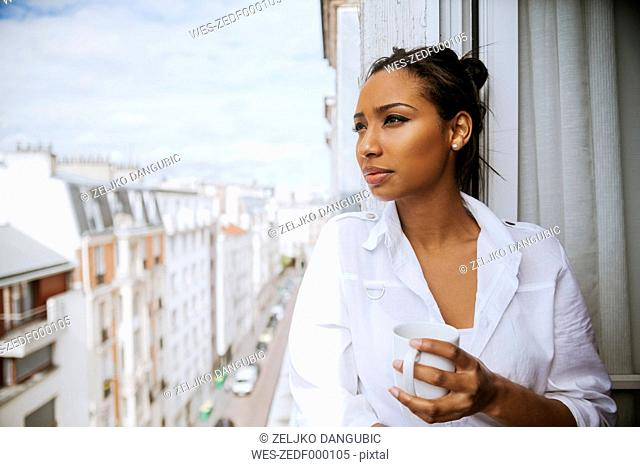 France, Paris, portrait of young woman with cup of coffee looking at distance