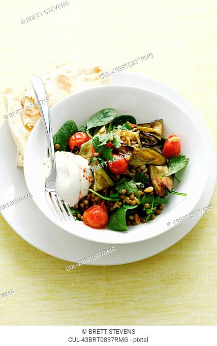 Bowl of salad with yogurt and bread