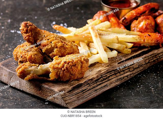 Fast food fried crispy chicken legs and french fries potatoes with salt served on wooden serving board over dark texture background. Space for text