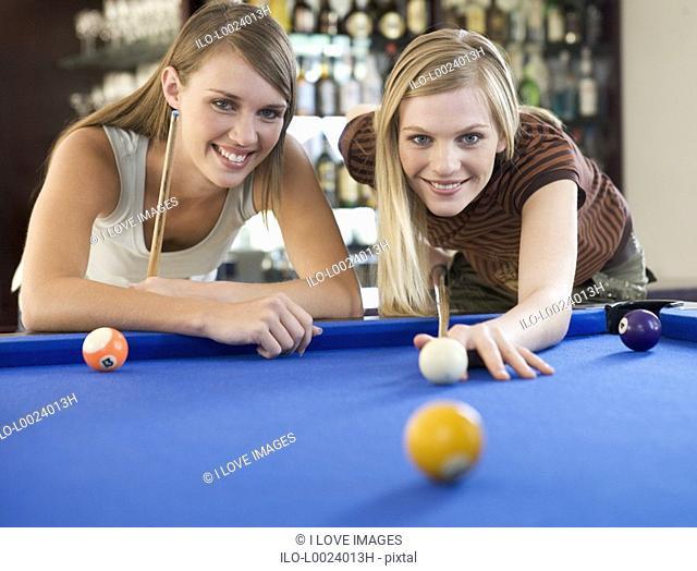 Two teenage girls playing pool