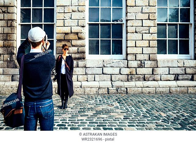 Rear view of man photographing woman standing against wall