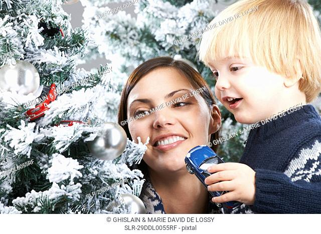 Mother and son decorating a xmas tree
