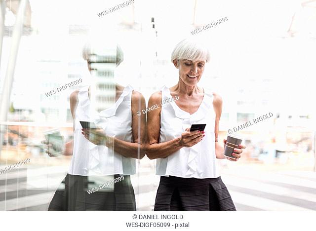 Smiling senior woman with cell phone and takeway coffee outdoors
