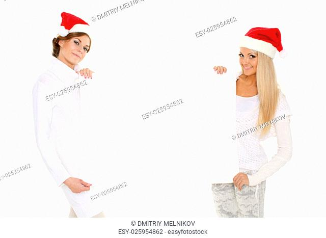 Two young pretty women in Santa Claus cap and winter clothes with empty board for the text on a white background. Christmas