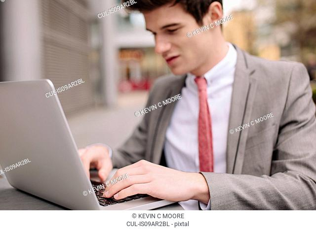 Young city businessman typing on laptop at sidewalk cafe