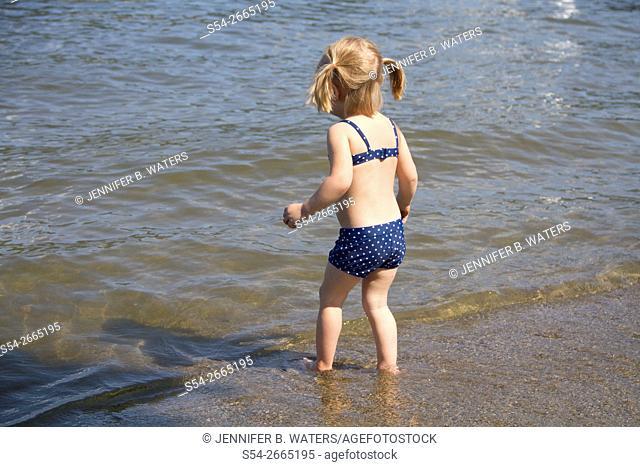 A girl plays in the water in Liberty Lake, Washington, USA