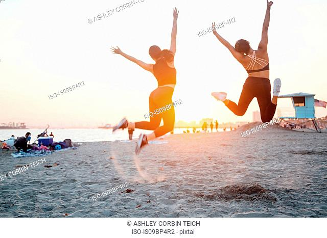 Friends jumping on beach, Long Beach, California, US
