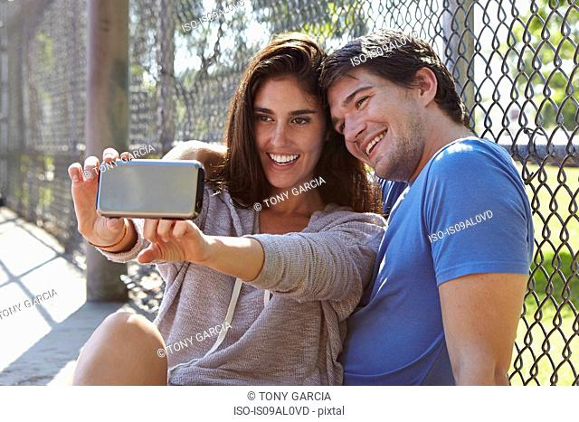 Young couple taking selfie by wire fence