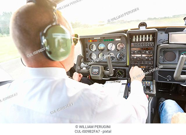 Rear view of pilot in cockpit of aircraft, in flight