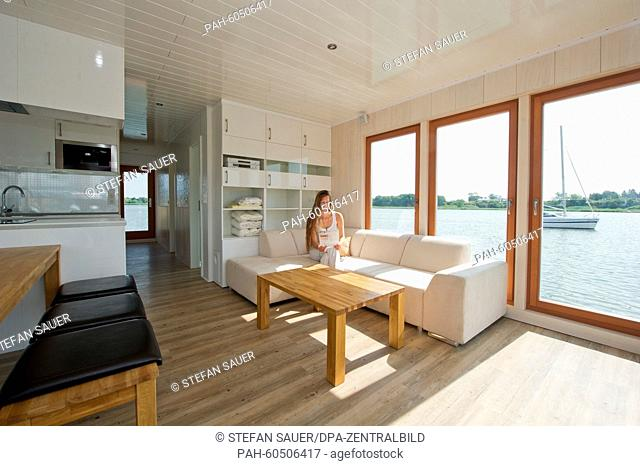 A staff member sits inb the living room area on a couch on a house boat of 'Hausboot Werft Peenestrom GmbH', manufacturer for tourist house boats