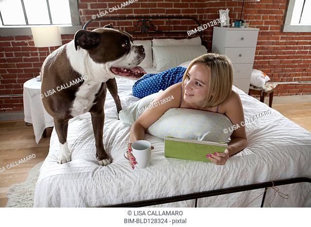 Caucasian woman relaxing with dog on bed