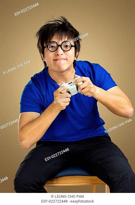 Asian man play tv game with brown background