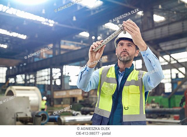 Male worker examining steel part in factory