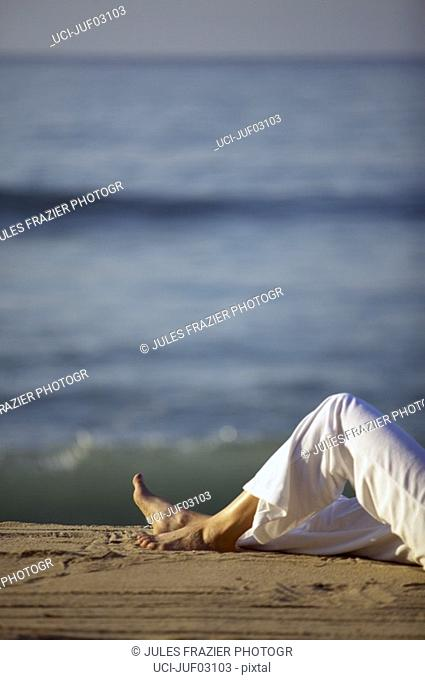 Woman digging feet into sand at beach