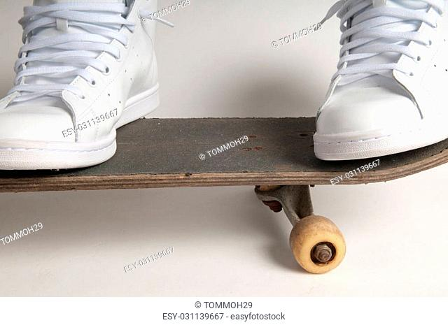 Man in clean white trainers doing tricks on an old skateboard