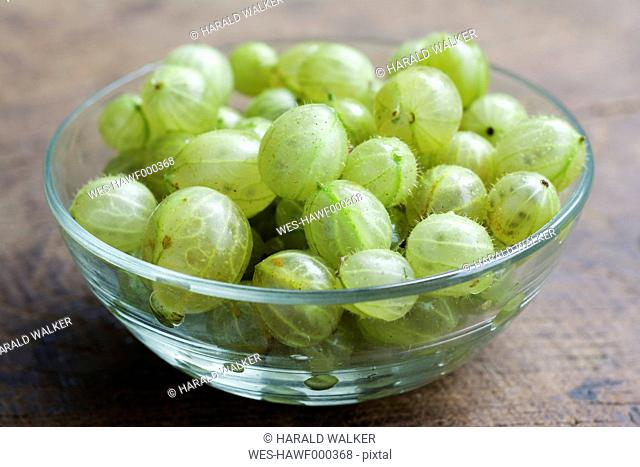 Glass bowl of gooseberries on wood, close-up