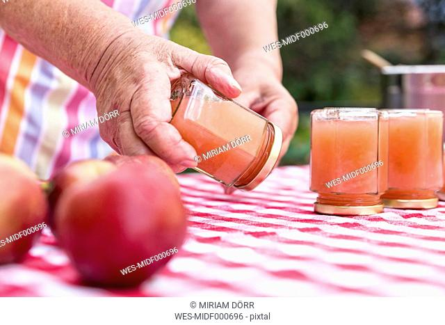 Senior woman turning glass of homemade applesauce, close-up