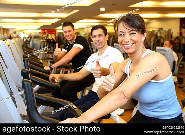 Two man and a woman on exercise bike showing thumbs up