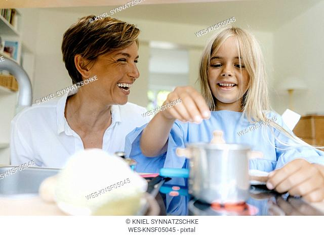 Happy mother and daughter playing with toy kitchen at home