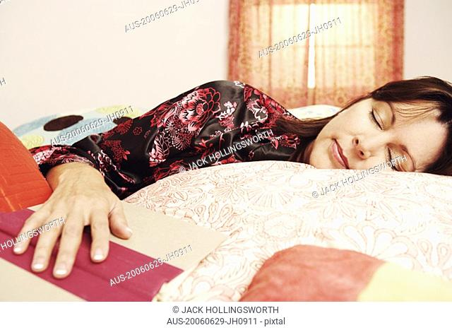 Close-up of a mature woman sleeping on the bed with her hand on an open book