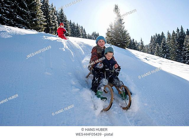 Children tobogganing in the snow