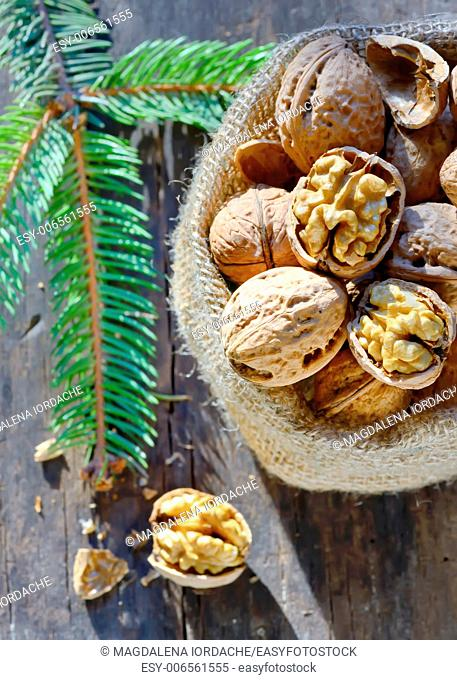 walnuts isolated in burlap bag on wooden background