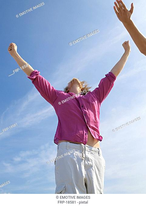 Young man on the beach raising his arms in the air