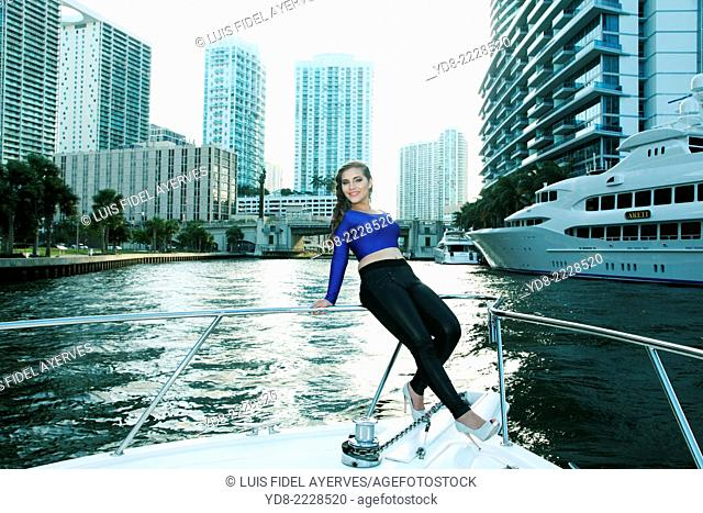 Quinceañera Young posing on the bow of a yacht off the coast of Miami, Florida, USA