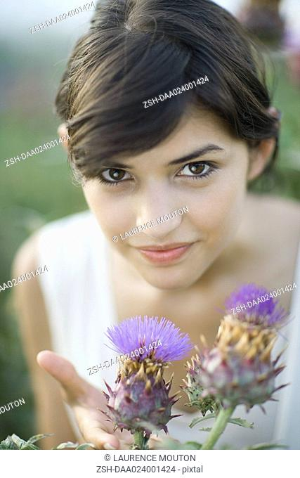 Young woman smelling thistle flowers