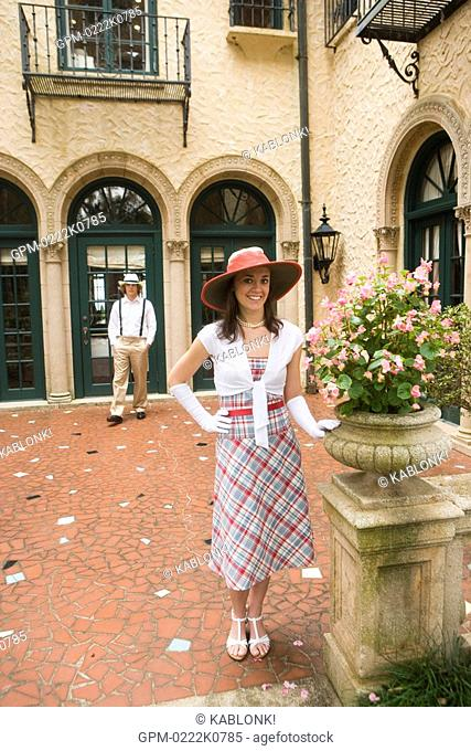 Portrait of stylish young woman wearing hat standing outside on patio, man in background