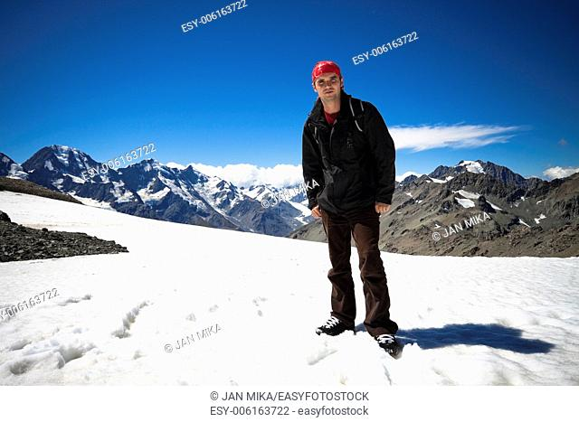 Young man standing on peak of Mount Cook the highest mountain in New Zealand, reaching 3,754 meters Mount Cook National Park, Southern Alps, South Island